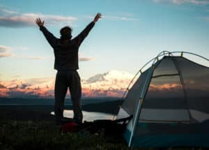 man camping with tent looking at mountains
