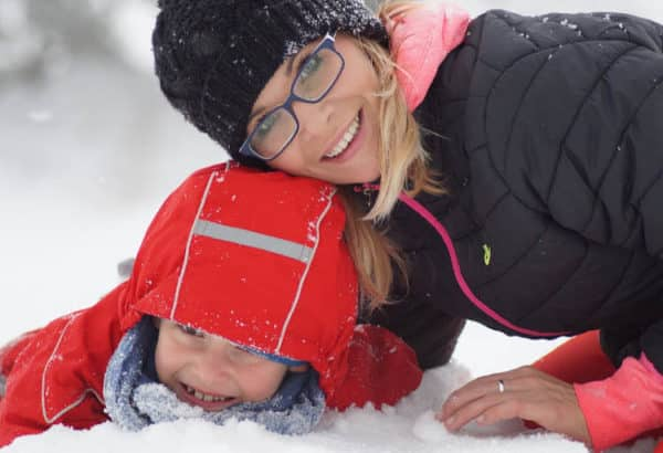heated jacket woman with child playing in snow