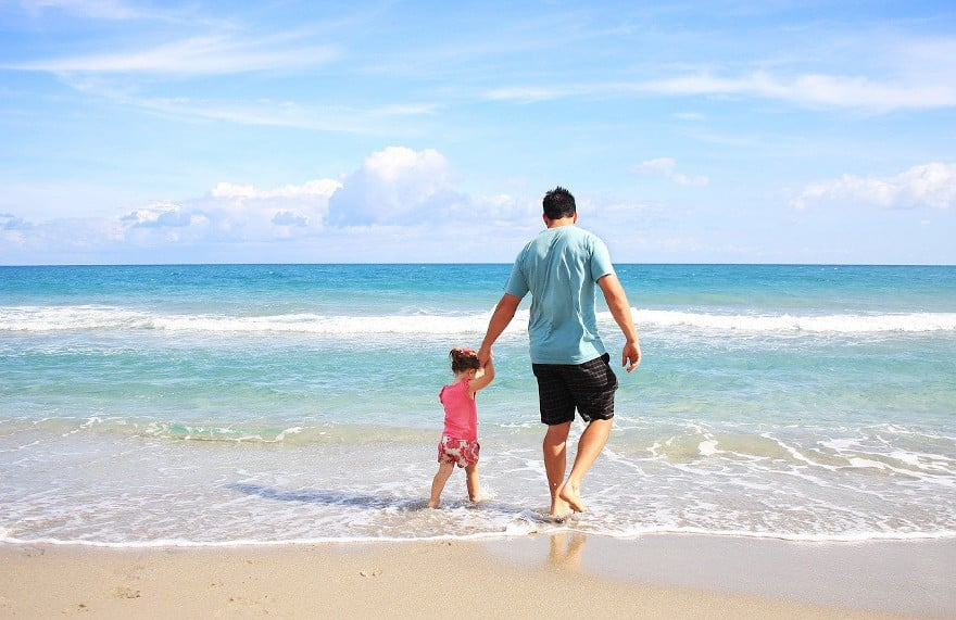 father-daughter-walking-on-beach