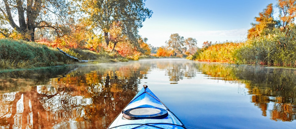 View from the blue kayak on the river banks with autumnal yellow leaves trees in fall season. The Seversky Donets river, autumn kayaking. View over nose of bright blue kayak.